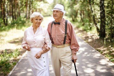 Photo pour Couple de personnes âgées en smart casual-wear marche dans le parc d'été - image libre de droit