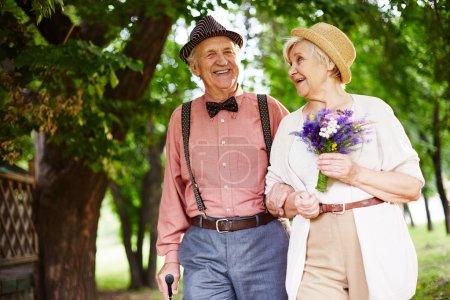 elderly couple walking in park
