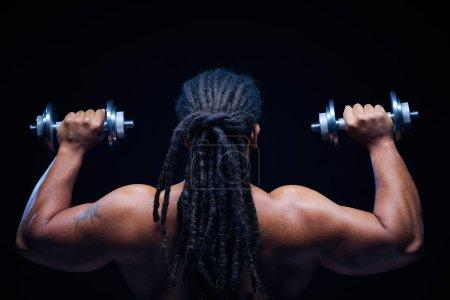 Photo pour Vue arrière de l'athlète africain musclé avec dreadlocks levant des cloches - image libre de droit
