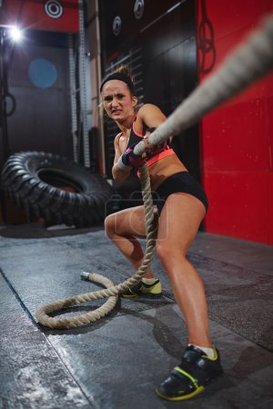 Photo for Active young woman pulling rope in gym - Royalty Free Image