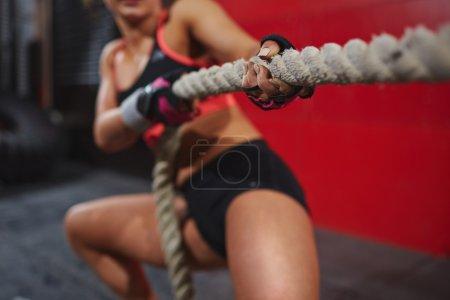 Photo pour Jeune femme active tirant la corde dans la salle de gym - image libre de droit