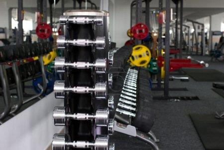 Photo pour De nombreux haltères et autres équipements sportifs dans le gymnase sur fond flou - image libre de droit