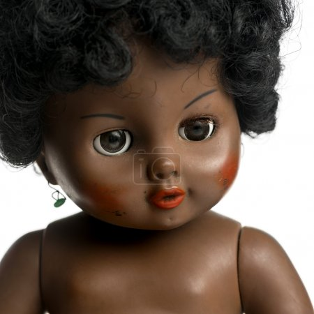 Used black doll in front of a white background
