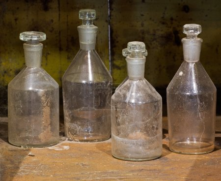 The old Reagent glass bottles on dusty table