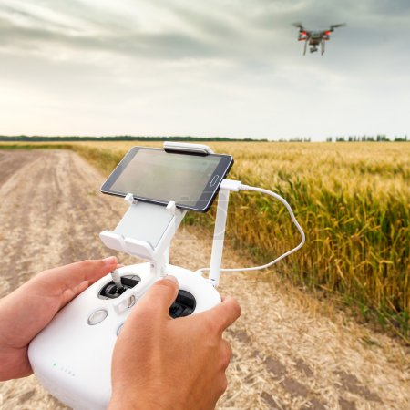 Photo for Demonstration of unmanned copter. Man controls quadrocopter flight. Flying the copter over a field of wheat. Remote control in a mans hands. - Royalty Free Image
