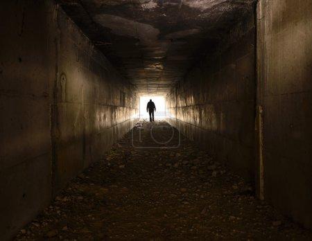 A man walking alone in the dark tunnel...