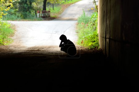 waif sitting in the tunnel in sorrow