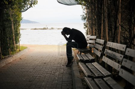 Photo for Depressed young man sitting on the bench - Royalty Free Image