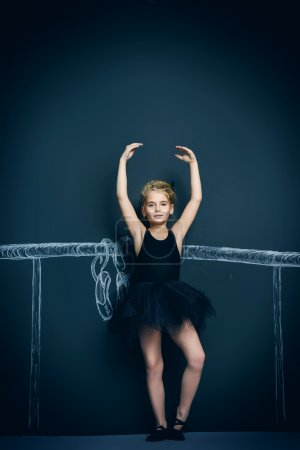 Photo for Beautiful girl ballet dancer in black leotard and tutu posing in studio over black background. - Royalty Free Image