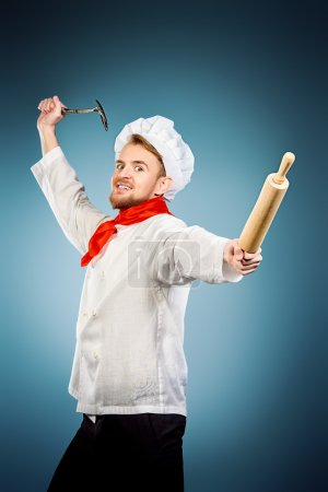 Photo for Enraged chef cook brandishing with ladle and a rolling pin. Studio shot. - Royalty Free Image
