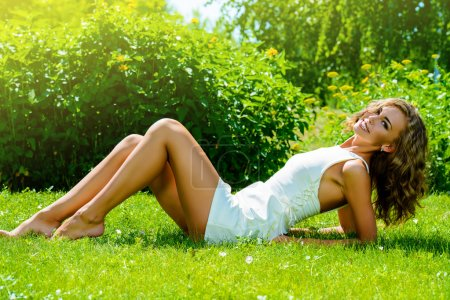 Photo for Happy beautiful girl in bright summer dress lying on a green lawn in the summer park. Beauty, fashion. Holidays. - Royalty Free Image