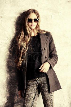 Photo pour Belle adolescente en vêtements d'automne posant par un mur grunge. Mode saisonnière. Style jeunesse . - image libre de droit