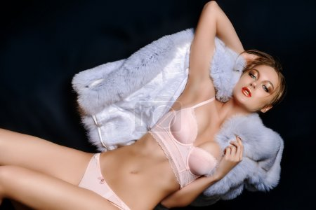 Photo for Sexual young woman in a beautiful pink lingerie lying on a white fur over black background. - Royalty Free Image
