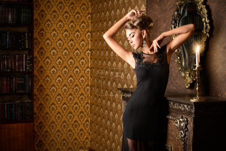 Photo for Elegant young woman in black evening dress posing in vintage interior. Fashion shot. - Royalty Free Image