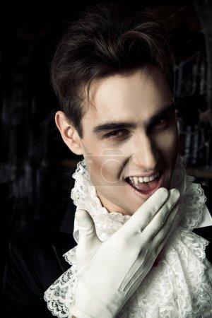 Photo pour Un bel homme vampire portant un élégant tailcoat se dresse dans le vieux château médiéval. Halloween . - image libre de droit