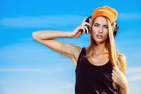Photo for Modern young woman listening to music on headphones outdoor. Trendy teenager girt over blue sky background. Youth style. - Royalty Free Image