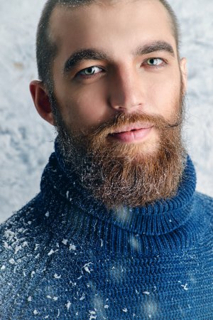 Photo for Portrait of a handsome brutal man with beard and mustache dressed in winter clothes, covered with snow. - Royalty Free Image