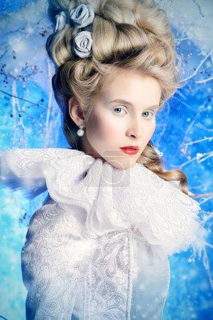 Photo pour Reine de glace fée en élégante robe argentée et blanche debout dans une forêt d'hiver magique. Beauté, mode . - image libre de droit