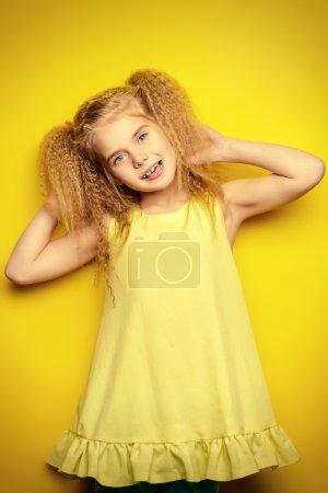 Foto de Niña alegre con hermoso cabello rubio sobre fondo amarillo. Estilo infantil. Peinado. - Imagen libre de derechos