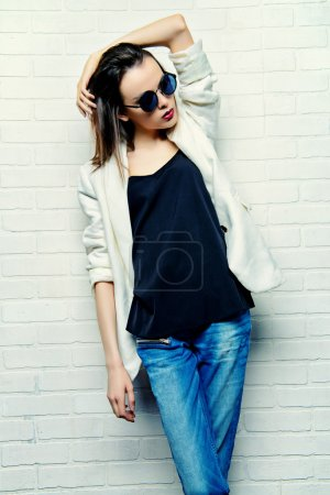 Photo for Modern brunette young woman in sunglasses posing by a white brick wall. Beauty, fashion. Youth style. - Royalty Free Image
