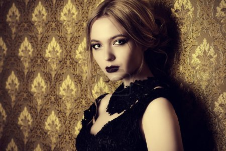 Photo for Evening look. Elegant young woman in black evening dress with dark make-up standing by a vintage wall. - Royalty Free Image