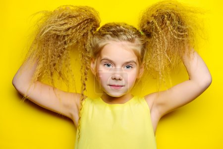 Photo for Joyful little girl with beautiful blonde hair over yellow background. Kid's style. Hairstyle. - Royalty Free Image