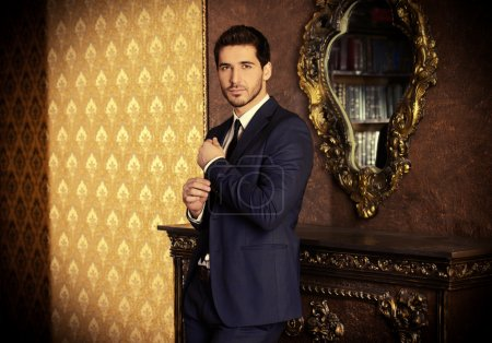 Foto de Joven respetable de pie junto a una chimenea en una habitación con interior clásico. Lujo. Belleza de los hombres, moda . - Imagen libre de derechos