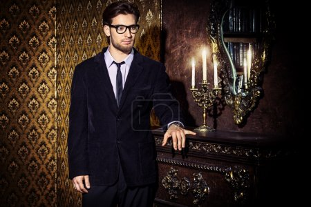 Photo for Handsome young man standing by a fireplace in a room with classic interior. Luxury. Men's beauty, fashion. - Royalty Free Image