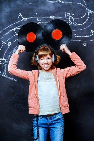 vinyl records. Cheerful teen girl enjoys the music.