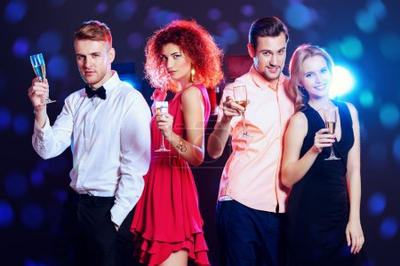 Photo for Cheerful young people dancing in a party club and drinking champagne. Holidays, celebration. - Royalty Free Image