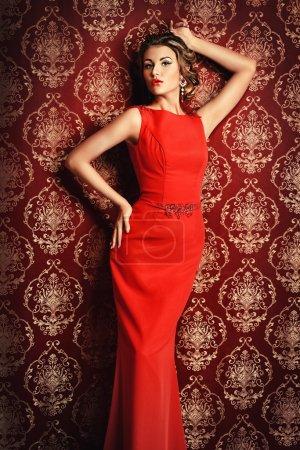Photo pour Portrait d'une femme élégante mince dans une belle robe rouge posant par papier peint vintage. Luxe, mode de vie riche. Des bijoux. Coup de mode . - image libre de droit