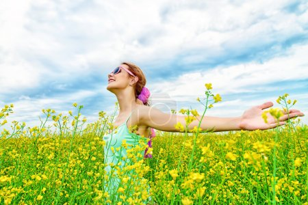Photo for Happy smiling girl at a yellow meadow on a sunny summer day. Smiling young woman outdoor. Holidays, summer vacation. - Royalty Free Image