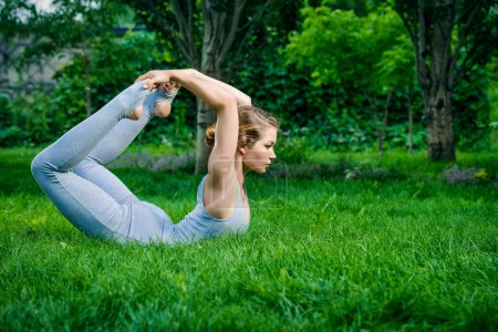 Photo for Beautiful young woman doing yoga in the summer park. Healthy lifestyle. Various yoga postures. - Royalty Free Image