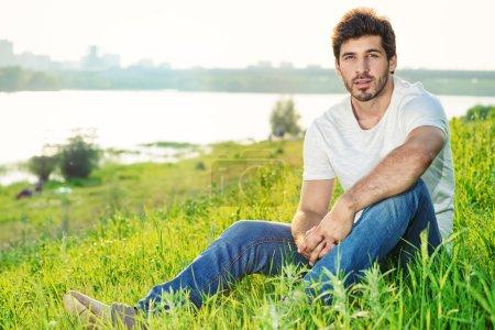 Photo pour Beau jeune homme debout sur une pelouse verte sur fond urbain . - image libre de droit