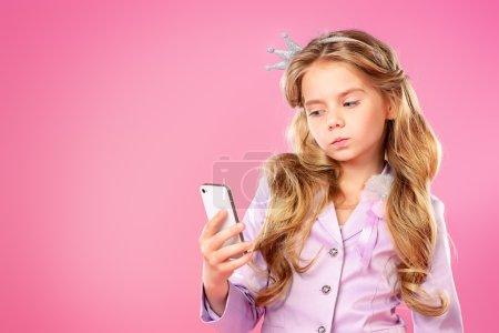 Photo pour Jolie petite fille avec beaux cheveux blonds faisant selfie sur fond rose. Petite princesse avec une couronne sur sa tête. Kids fashion. - image libre de droit