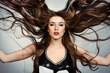 Photo for Portrait of a beautiful young woman with long fluttering hair. Hairdressing, hairstyle. Healthy long wavy hair. Sexy model with black smoky eyes. - Royalty Free Image