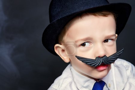 Photo for Funny little boy in father's hat plays with false mustache. Childhood concept. Emotions. - Royalty Free Image