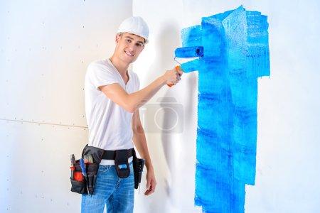 Photo pour Bel homme souriant peignant des murs dans de nouveaux appartements. Peintre professionnel masculin peint le mur en couleur bleue. Professions du bâtiment . - image libre de droit