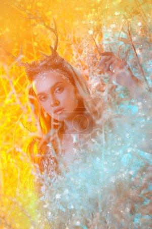 Portret czarującej leśnej nimfy w magicznym lesie. Zachodzące słońce w tle.