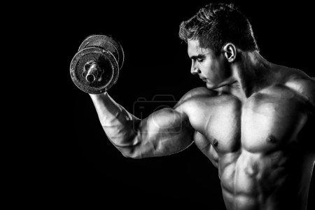 Photo pour Portrait d'un beau bodybuilder musclé posant avec des haltères sur fond noir . - image libre de droit