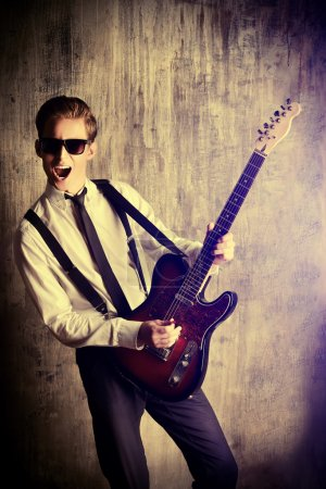 Photo for Expressive young man playing rock-n-roll music on his electric guitar. Retro, vintage style. - Royalty Free Image
