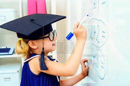 Photo pour Jolie petite étudiante en chapeau scolaire pendant la leçon à l'école. Concept éducatif . - image libre de droit
