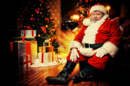 Photo for Santa Claus brought gifts for Christmas and sat down to rest by the fireplace. Home decoration. - Royalty Free Image