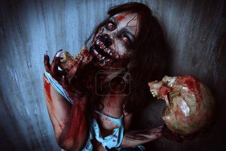 Foto de Chica de aterrador sangriento zombie con una calavera. Halloween. - Imagen libre de derechos