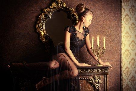 Photo pour Élégante jeune femme en robe de soirée noire posant à l'intérieur vintage. Coup de mode . - image libre de droit