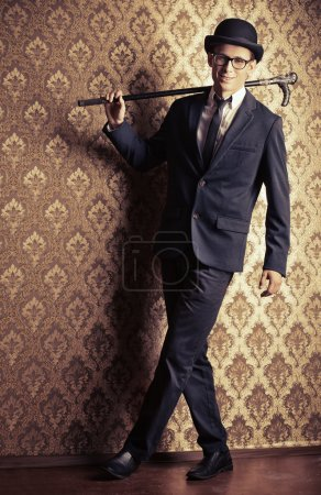 Photo for Portrait of a handsome young man in elegant suit and bowler hat posing over vintage background. - Royalty Free Image