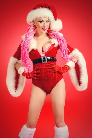 Photo for Pretty sexual babe dressed as Santa Claus posing over red background. Christmas. - Royalty Free Image