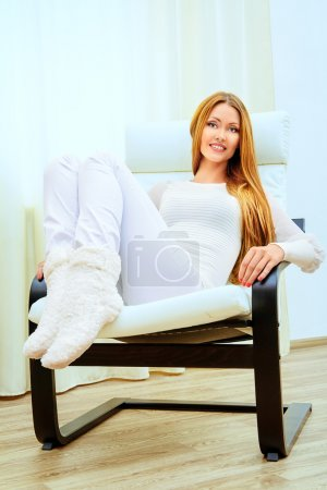 Photo for Happy young woman resting at home in a comfortable chair. - Royalty Free Image
