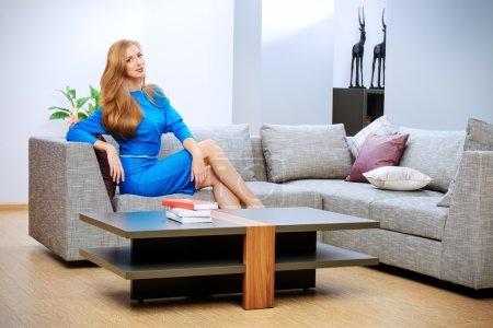 Photo pour Élégante jeune femme assise sur un canapé dans le salon. Intérieur . - image libre de droit