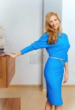 Photo pour Élégante jeune femme debout dans le salon de sa maison moderne. Beauté, mode. Intérieur . - image libre de droit